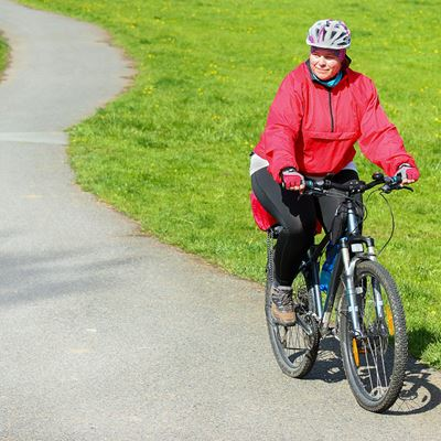Overweight woman is cycling on a bike path in the sun