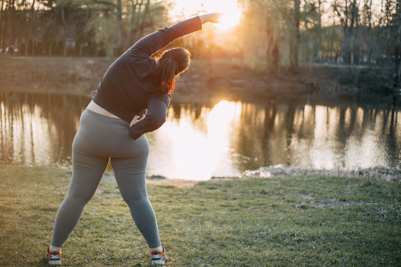 Obese woman stretching - sunset