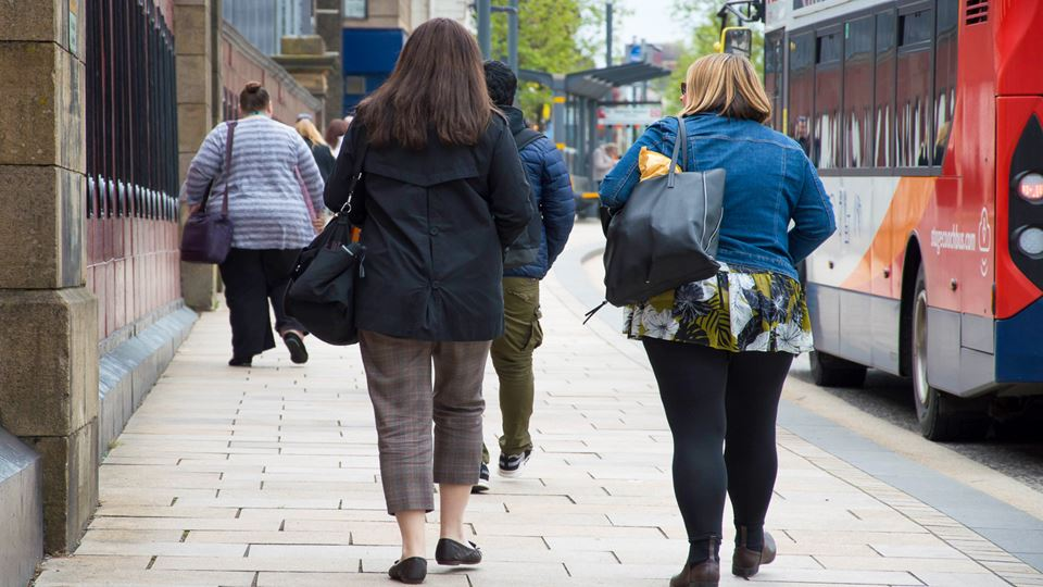 Two overweight women walk in city street while bus passes