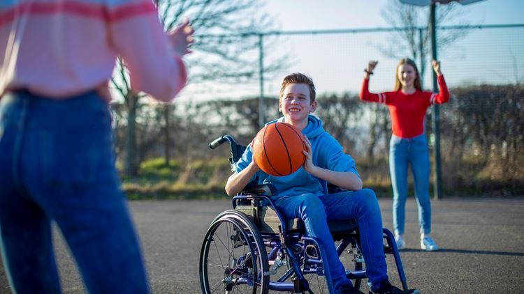 Boy in a wheelchair playing basketball