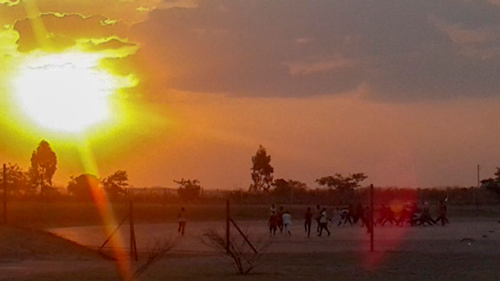 People playing football in Zambia at sunset