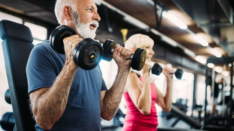 Elderly man holding a dumbbell in each hand