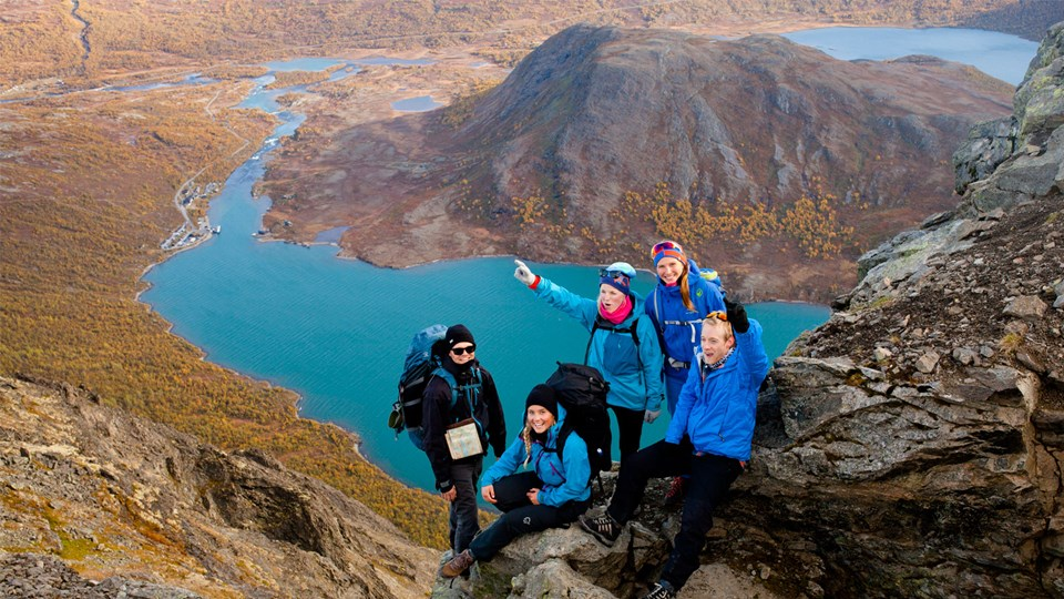 Five students hiking in the mountains looking over a lake